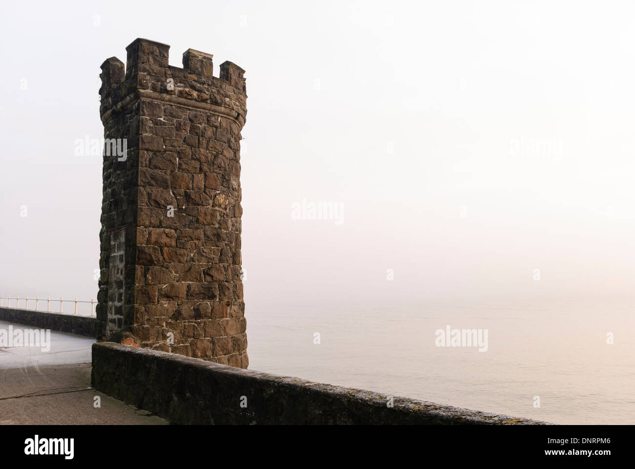 Stone castlated tower on a sea wall on a misty morning Stock Photo