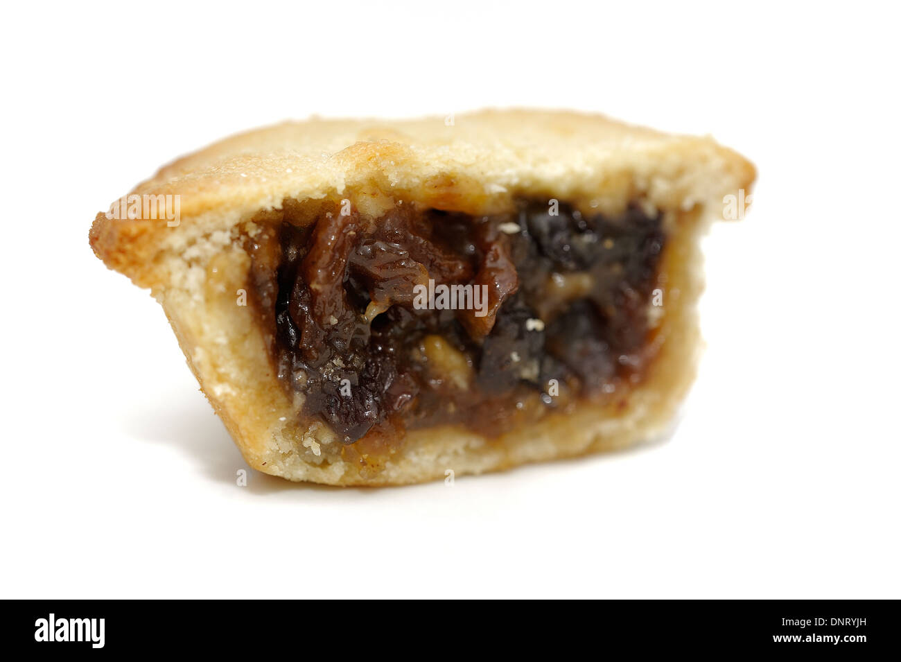 A festive Christmas mince pie cut in half to show the generous filling inside. - Stock Image