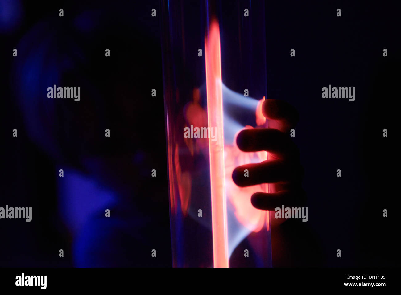 Electricity Arcs from a Plasma Ball - Tube - Globe - Lamp when child boy finger touch it - Stock Image