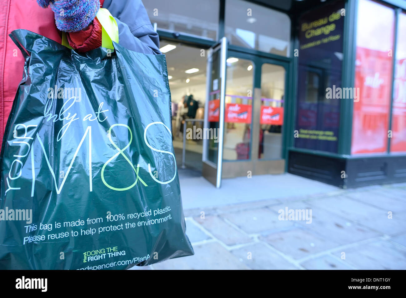 woman standing outside marks and spencer spencers chichester store shop north street  with holding recycled  M & S carrier bag - Stock Image