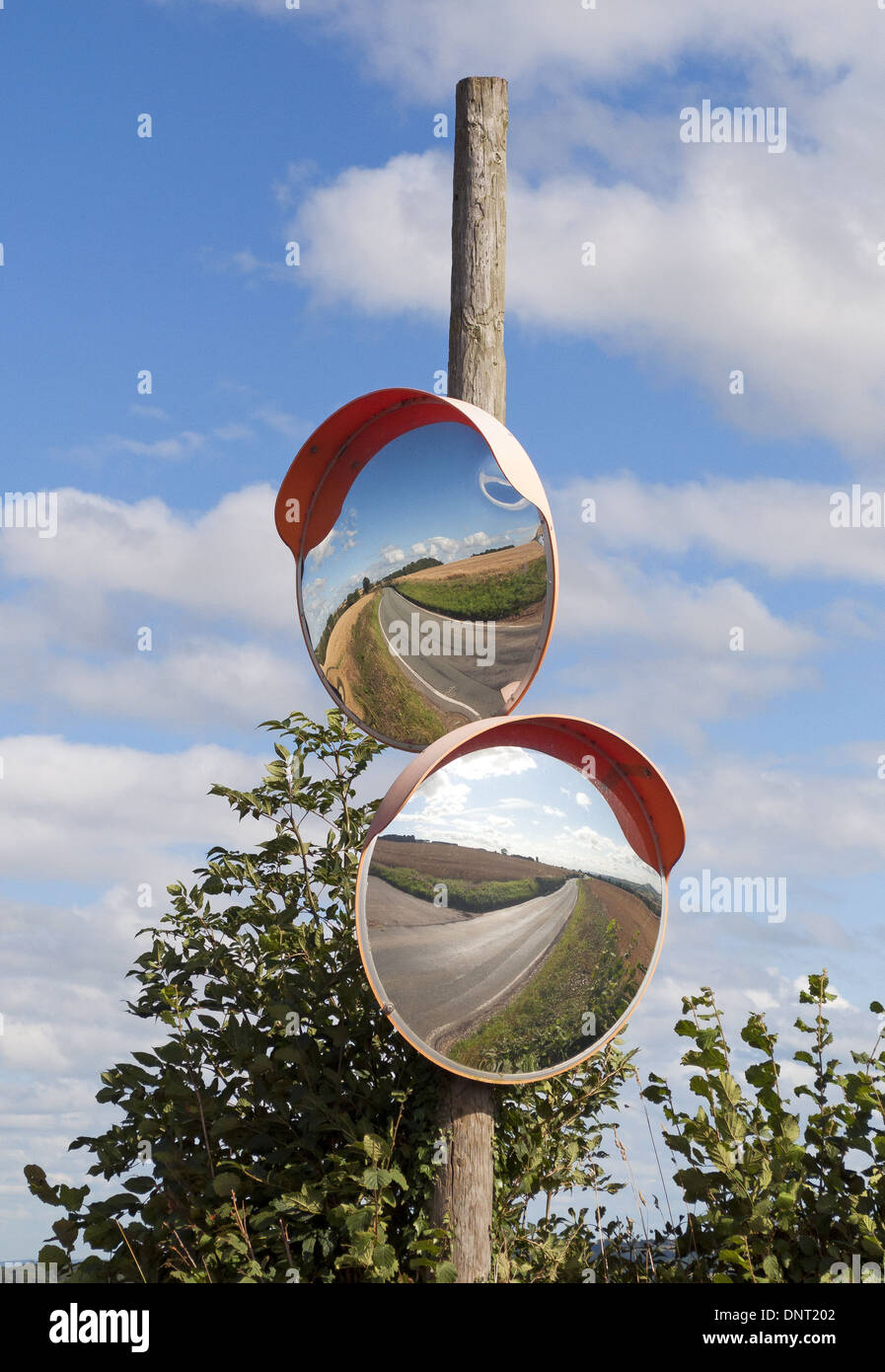 Two convex road safety mirrors on wooden post on a concealed entrance on a straight country road - Stock Image
