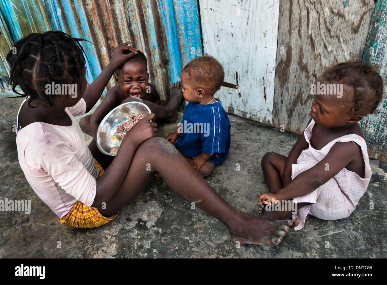 A girl feeds his younger brother by rice in the slum of Cité Soleil, Port-au-Prince, Haiti. - Stock Image