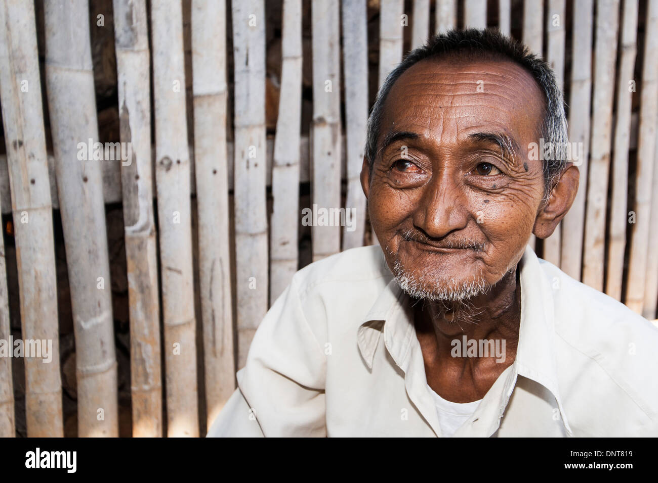 Elderly Asian man sits in front of a bamboo screen in a village on November 3, 2013 in a village on Inle lake, Myanmar. - Stock Image