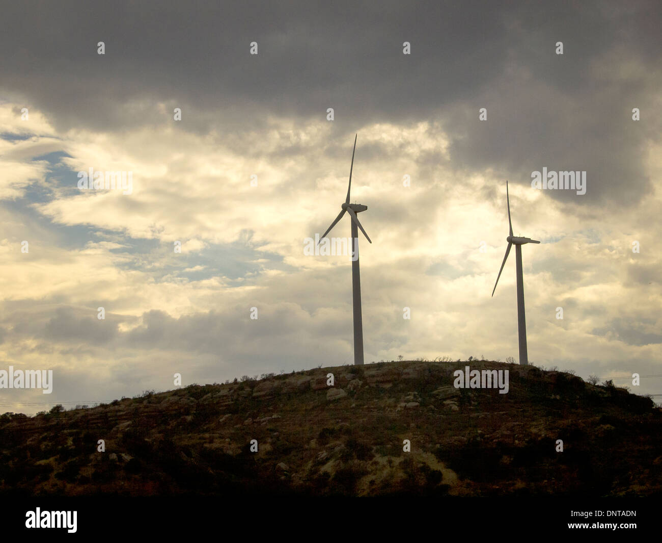 Wind turbines sit on hill in west Texas and face stormy weather as new discovery of fossil fuel competes with renewable energy. - Stock Image