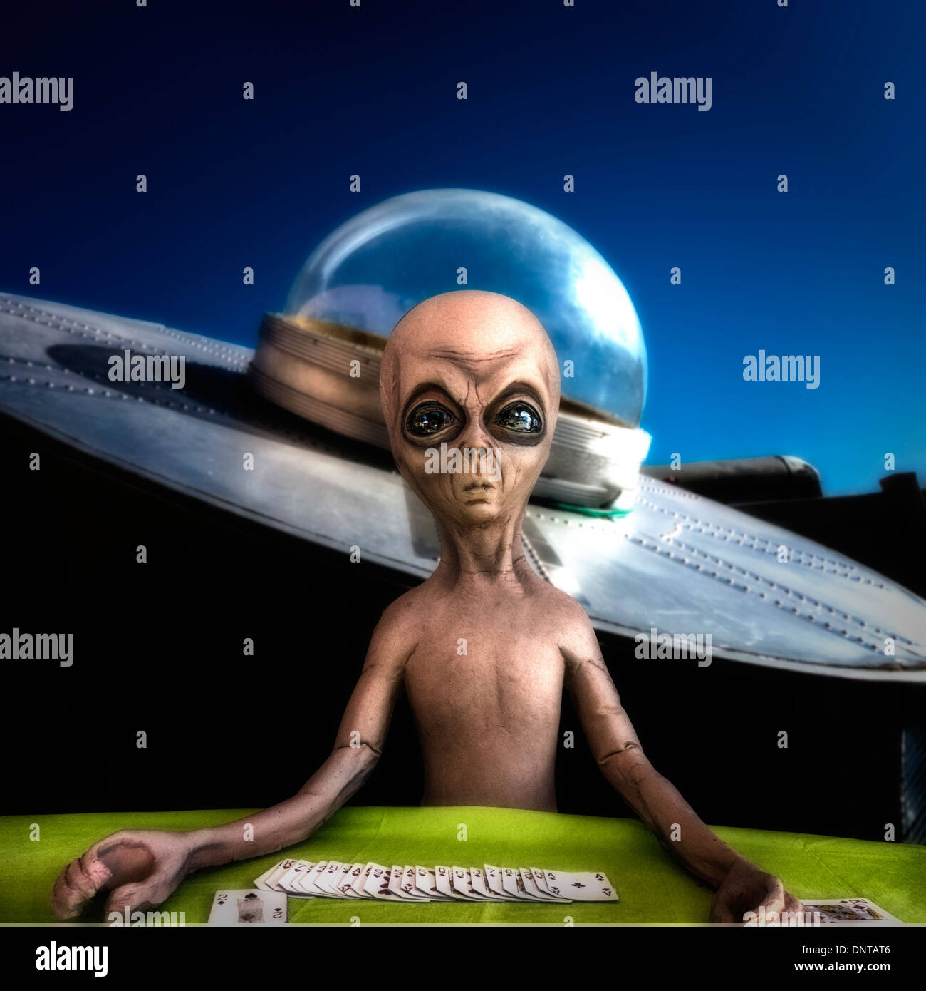 A composite humorous image of an alien black jack dealer and his space craft - Stock Image