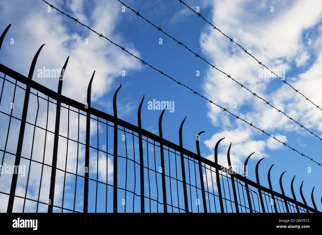 spiked and barb wire mesh fence silhouette - Stock Image