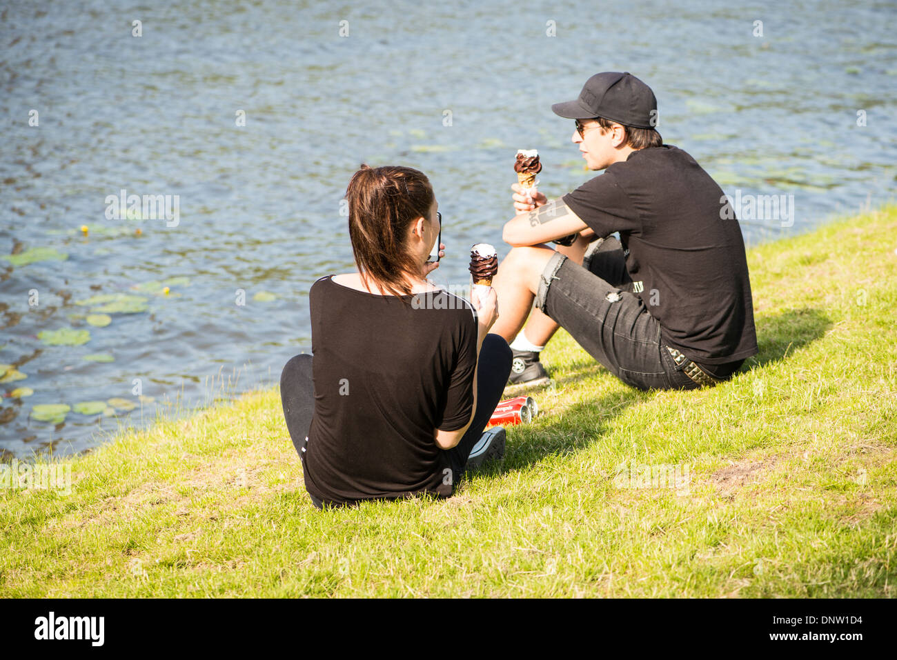 Young couple in black eating chocolate ice creams by the river. - Stock Image
