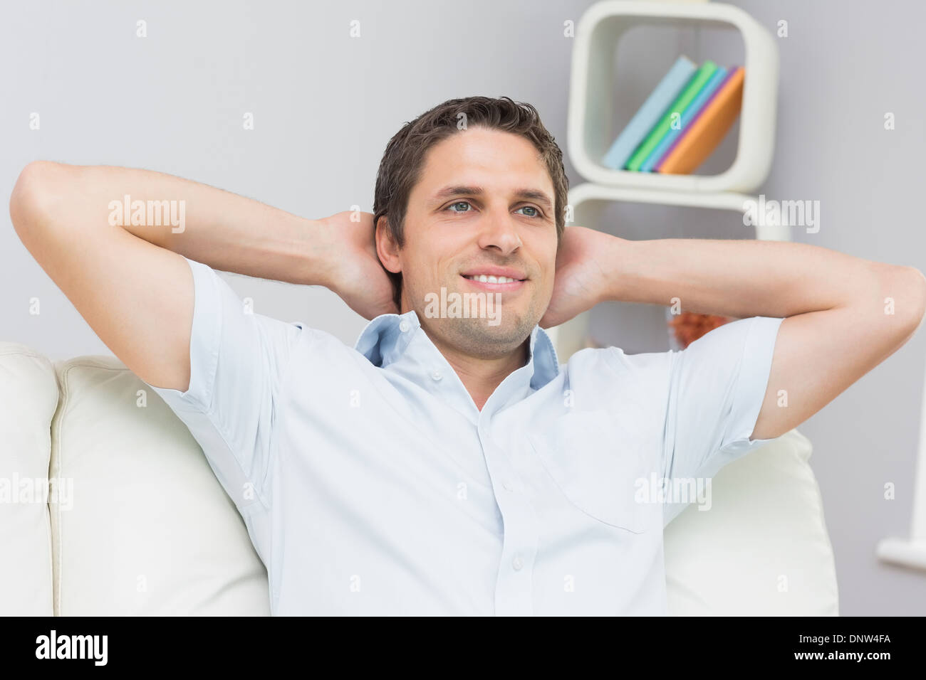 Thoughtful man sitting with hands behind head in the living room - Stock Image