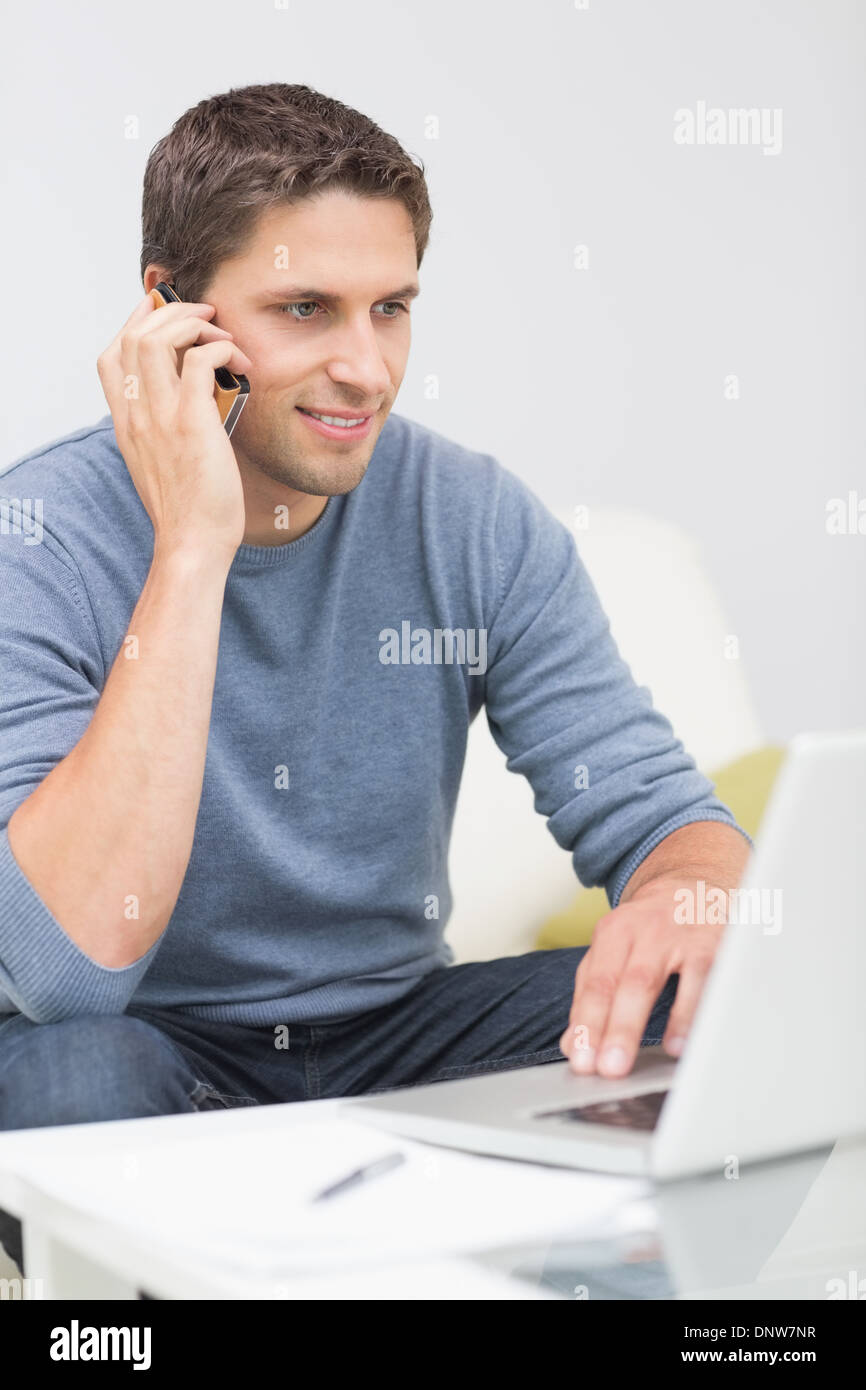 Man using cellphone and laptop in living room - Stock Image
