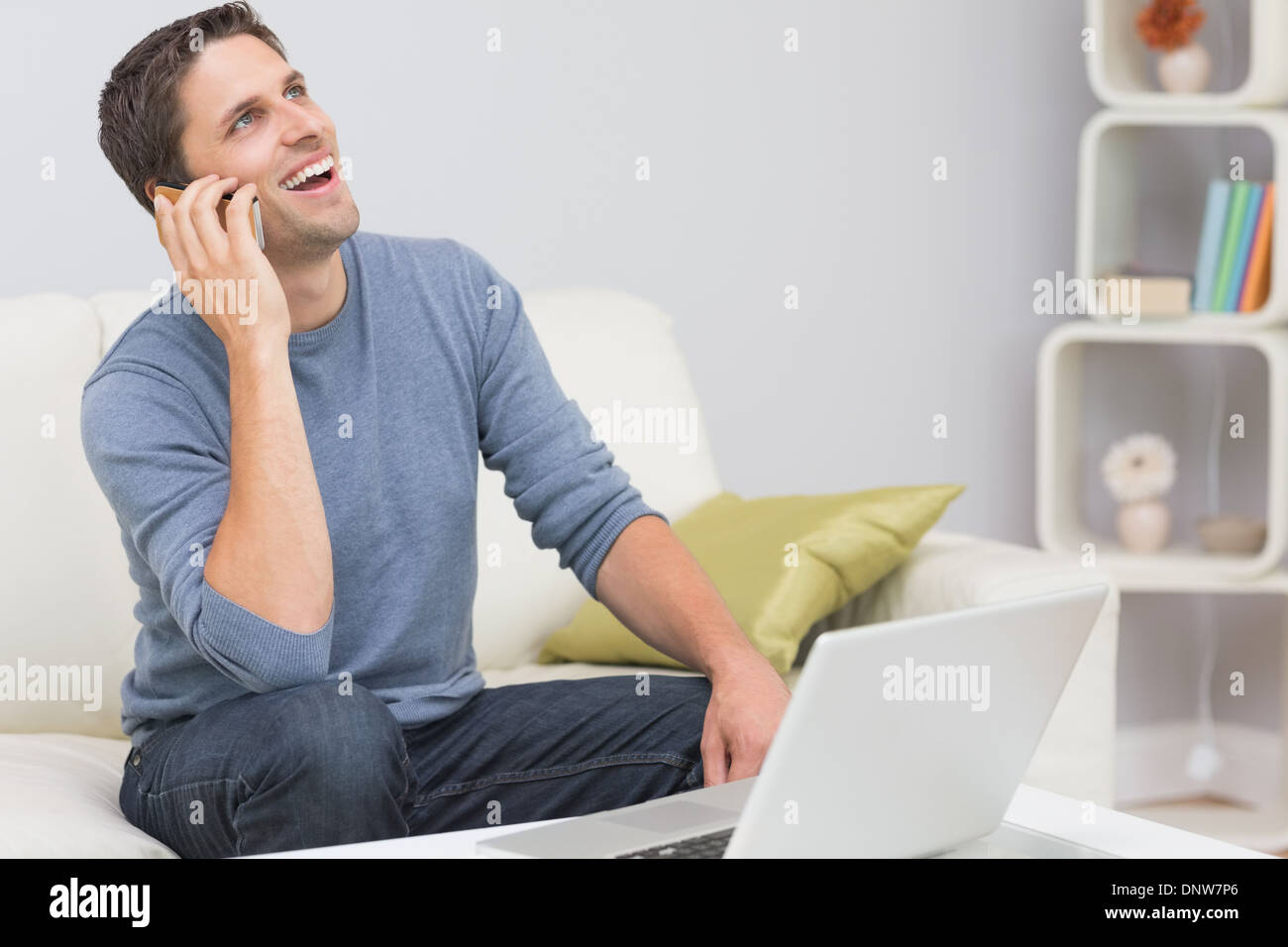 Cheerful man using cellphone and laptop in living room - Stock Image
