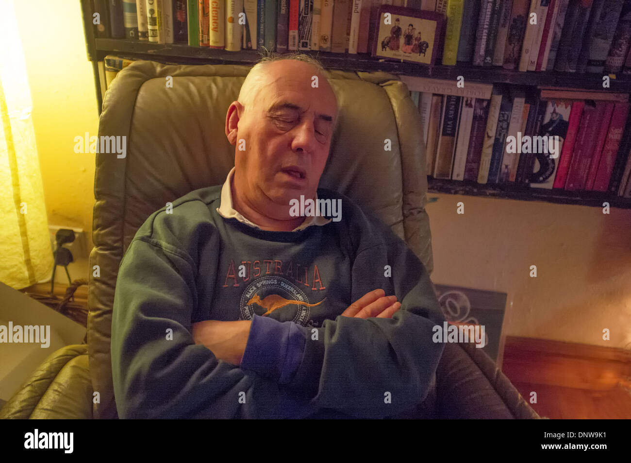 A  man in his 70's asleep in a chair - Stock Image