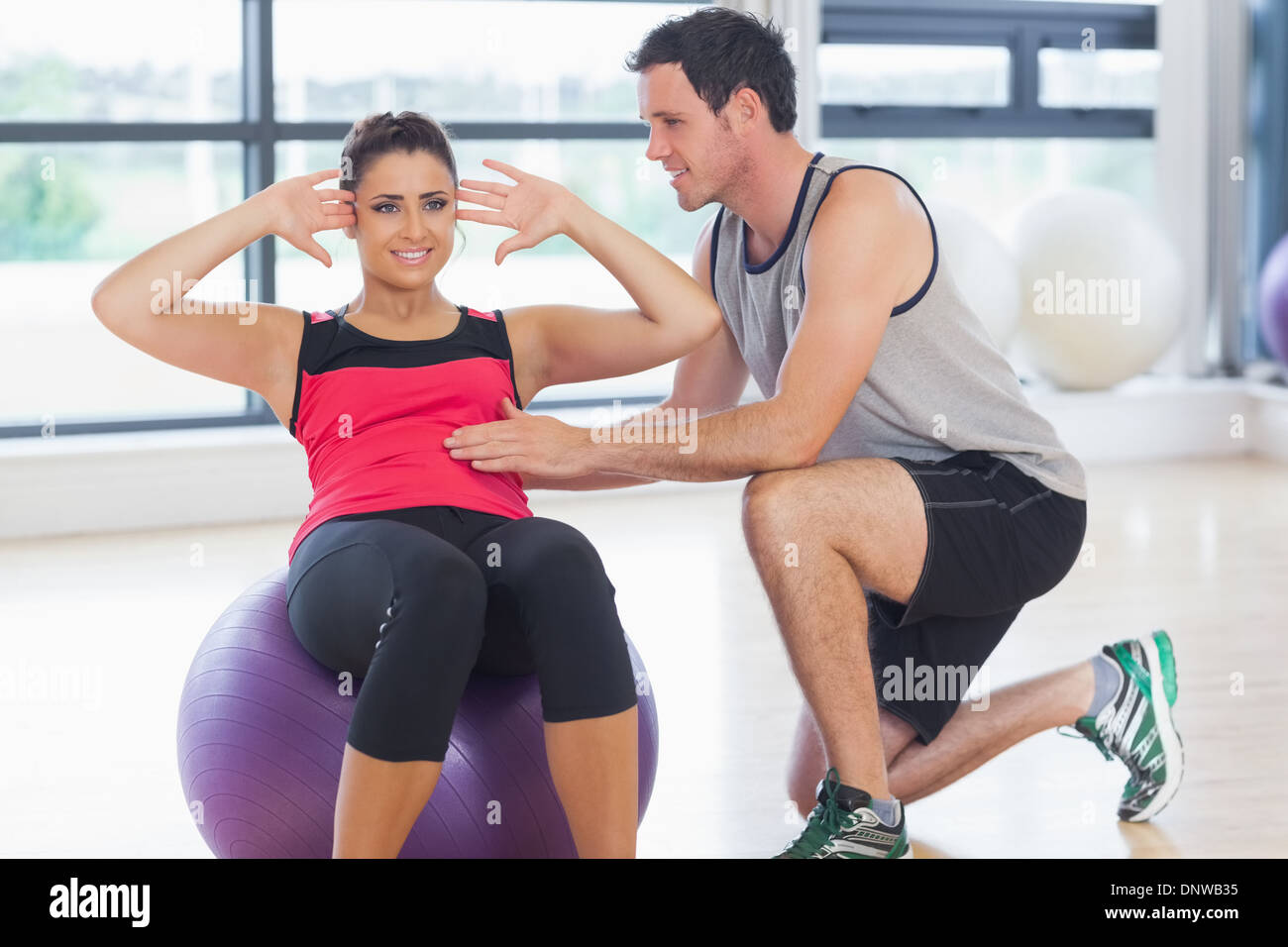 Trainer helping woman do abdominal crunches  on fitness ball - Stock Image