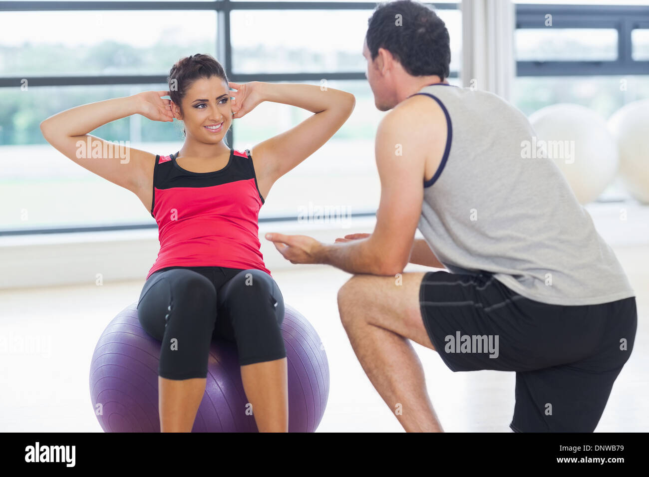 Trainer helping woman do abdominal crunches  on fitness ball Stock Photo