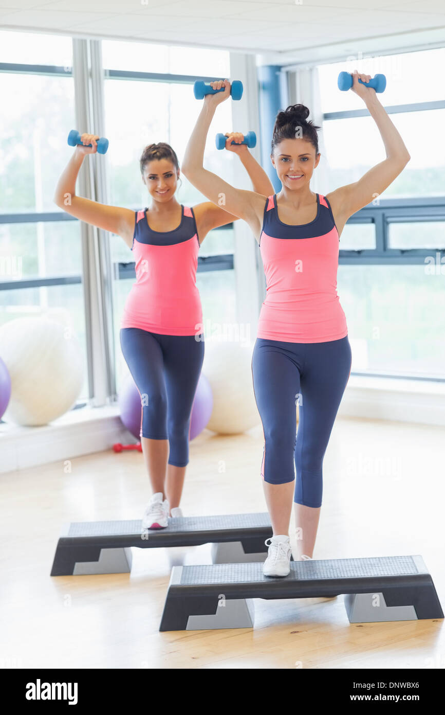 Two women performing step aerobics exercise with dumbbells - Stock Image