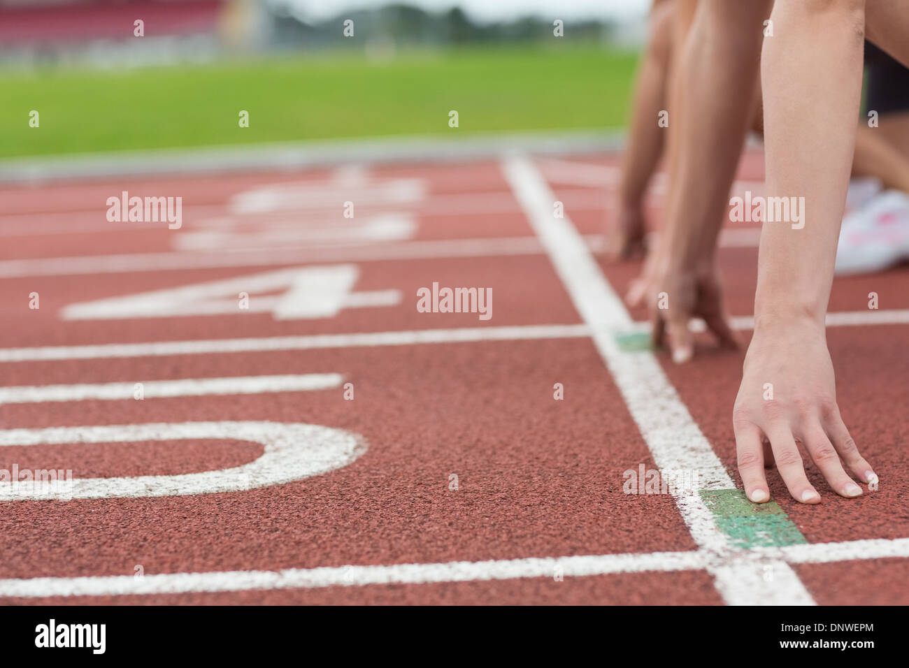 Cropped people ready to race on track field - Stock Image