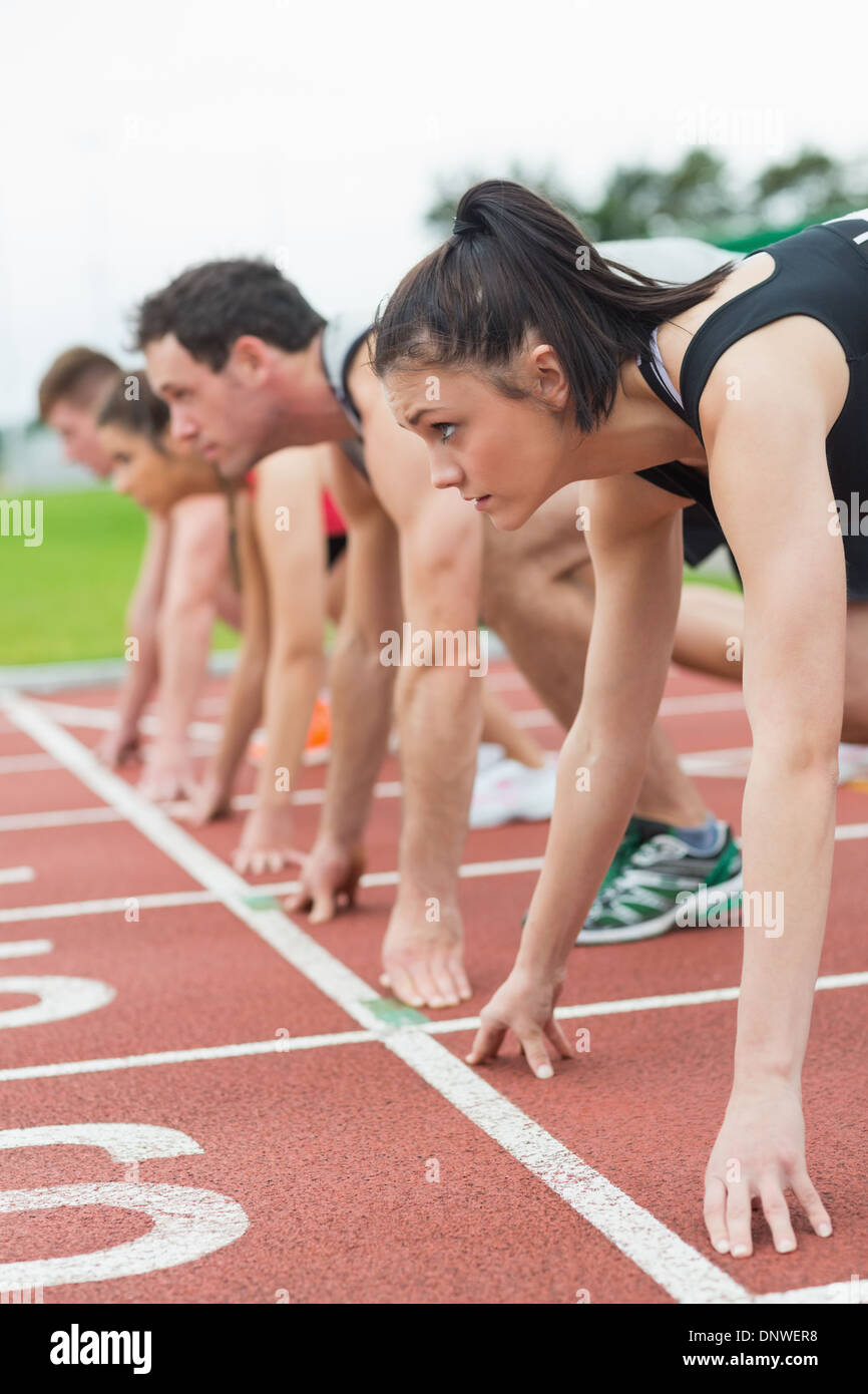 Young people ready to race on track field - Stock Image
