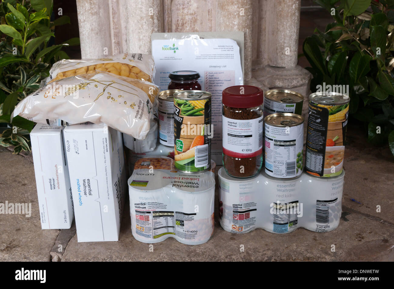 Food left on font of All Saints church at Upper Sheringham as donations to the Cromer & District Food Bank. - Stock Image