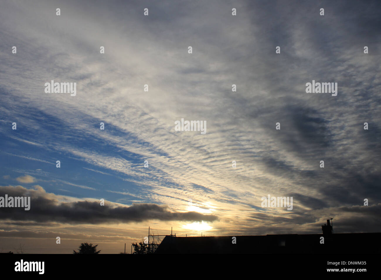 Interesting cumulus, cirrocumulus and cirrus cloud formations at sun rise on a winter's morning in Hampshire, UK - Stock Image