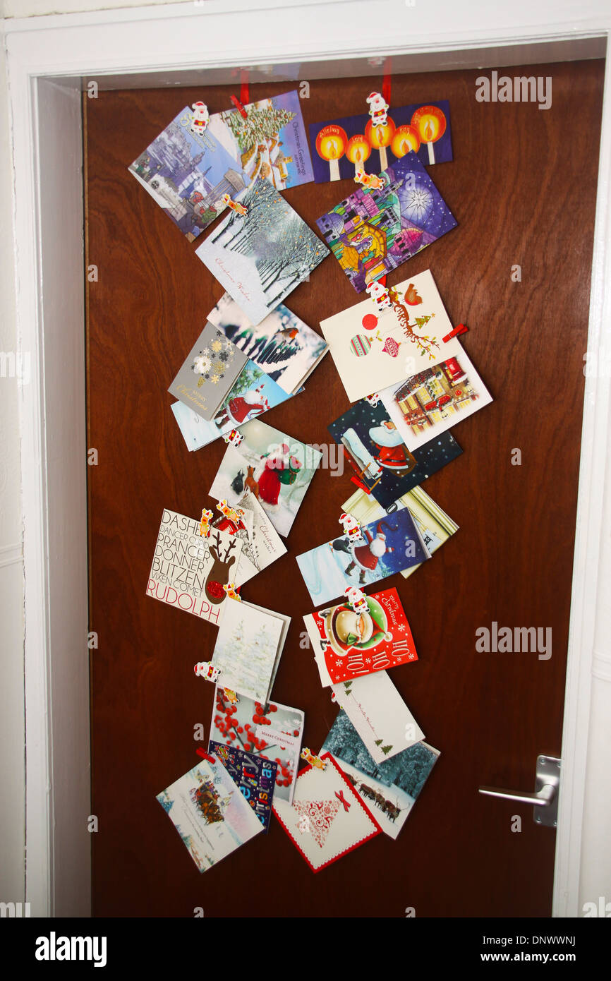 Christmas cards stuck on back of door - Stock Image