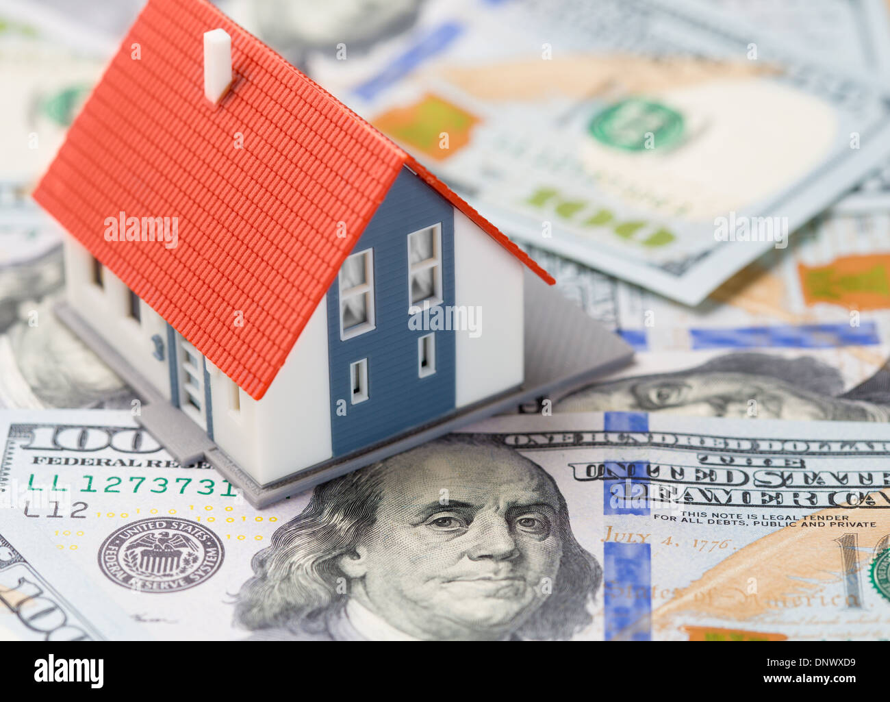 Small house over dollars banknotes. Mortgage concept. - Stock Image