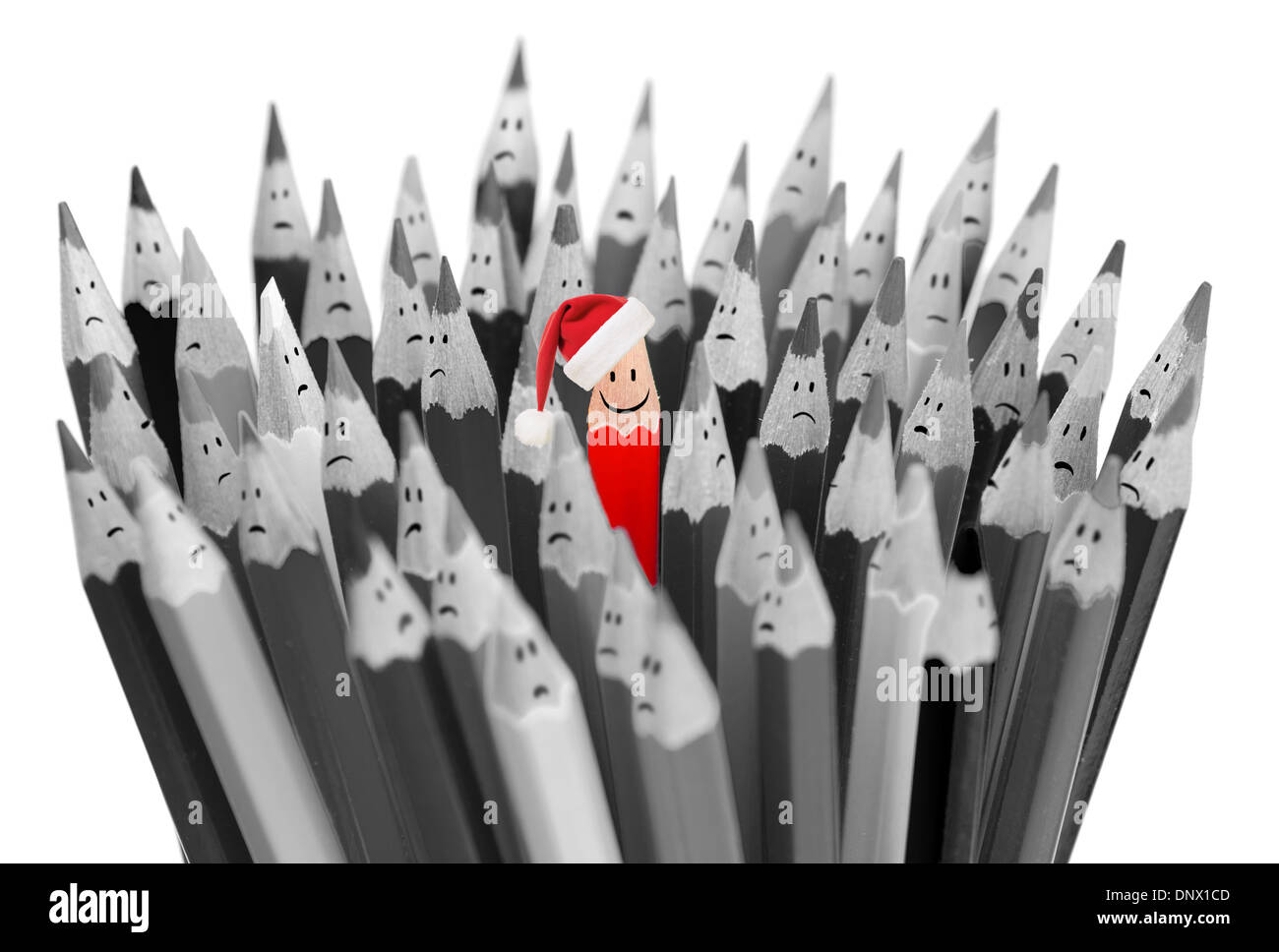pencil with smile in Santa's Christmas hat among sad gray pencils - Stock Image