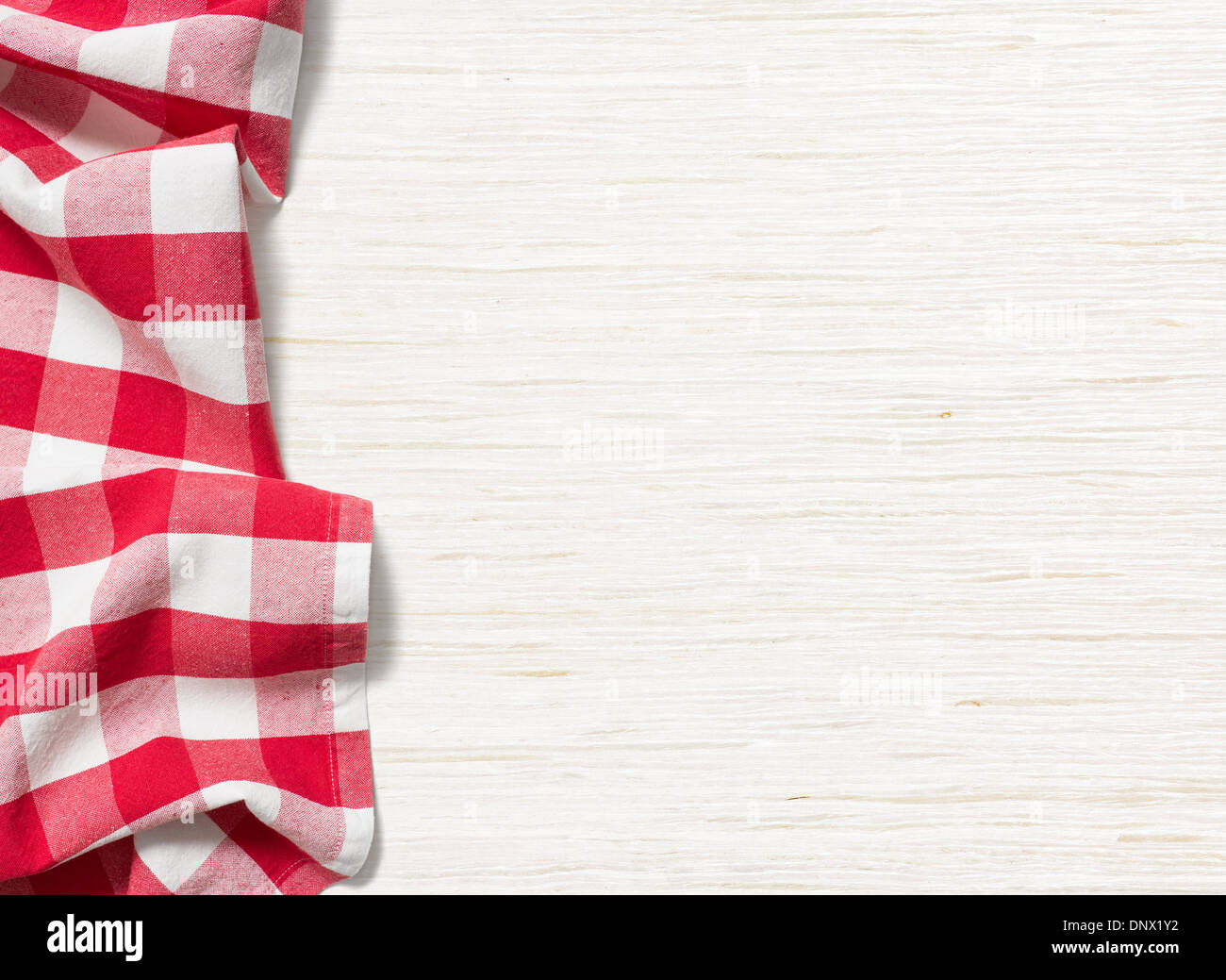 red folded tablecloth over bleached wooden table - Stock Image