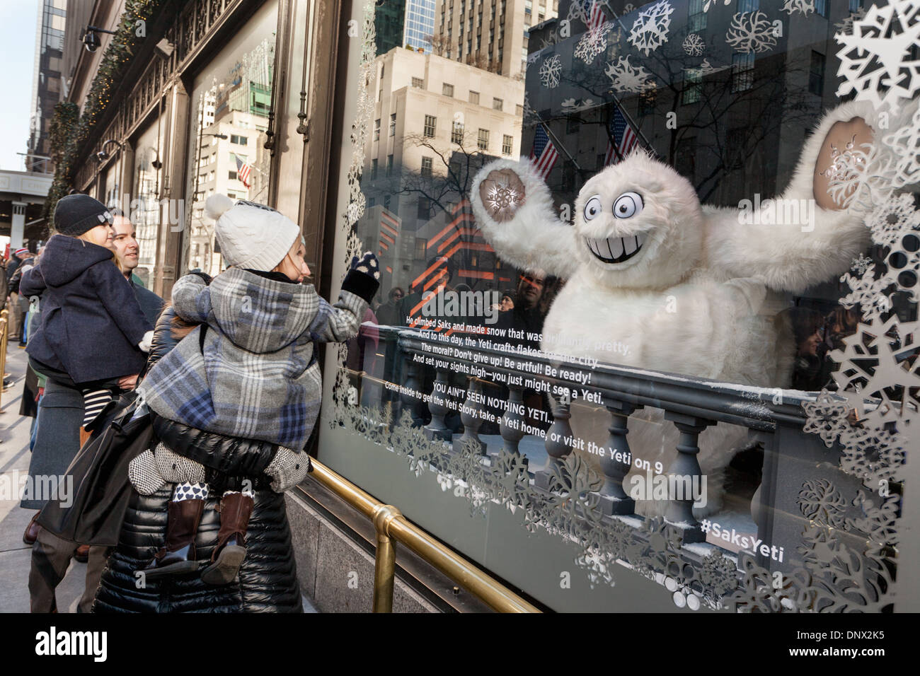 Children and parents marvel at Christmas windows, Saks Fifth Avenue, New York City. - Stock Image
