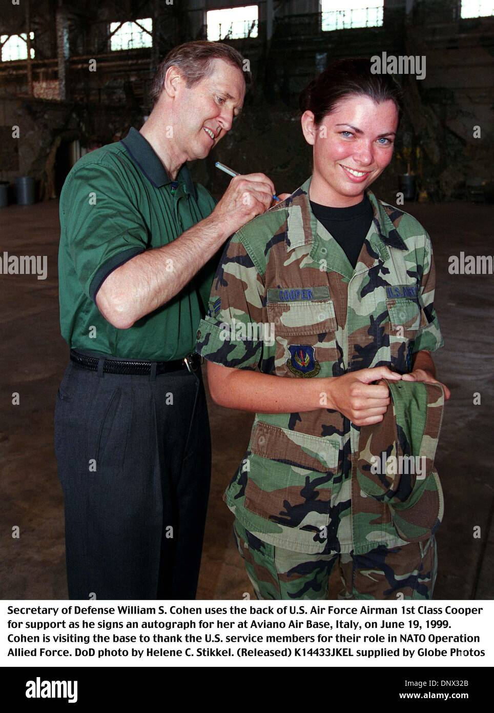 June 19, 1999 - K14433JKEL    06/19/99.990619-D-2987S-082..Secretary of Defense William S. Cohen uses the back of U.S. Air Force Airman 1st Class Cooper for support as he signs an autograph for her at Aviano Air Base, Italy, on June 19, 1999.  Cohen is visiting the base to thank the U.S. service members for their role in NATO Operation Allied Force.  DoD  Helene C. Stikkel.  (Relea - Stock Image