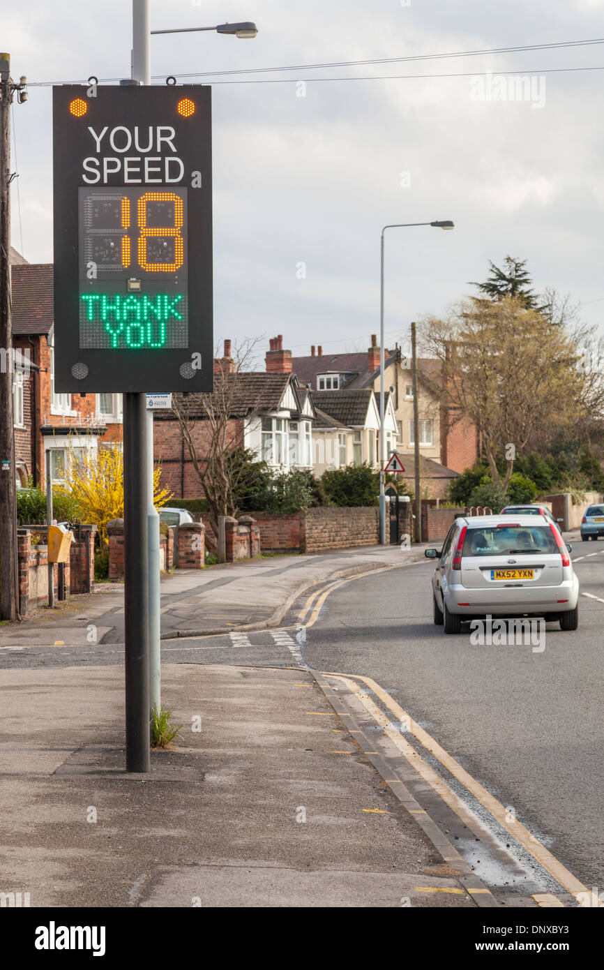 Traffic speed warning indicator by the road with a car well within the speed limit, England, UK - Stock Image