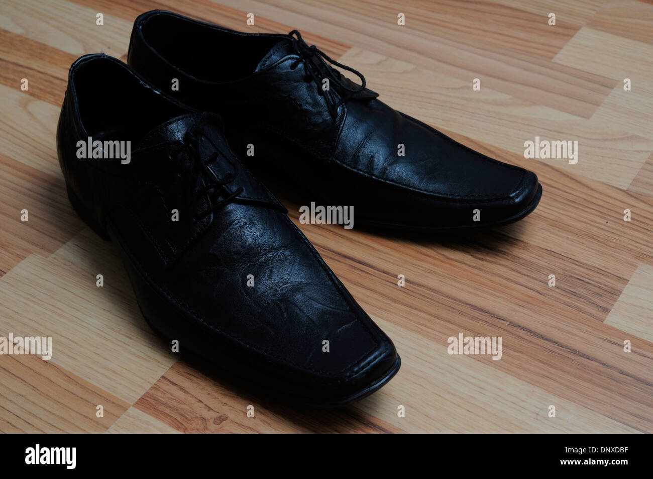 Black dress shoes on the floor. - Stock Image