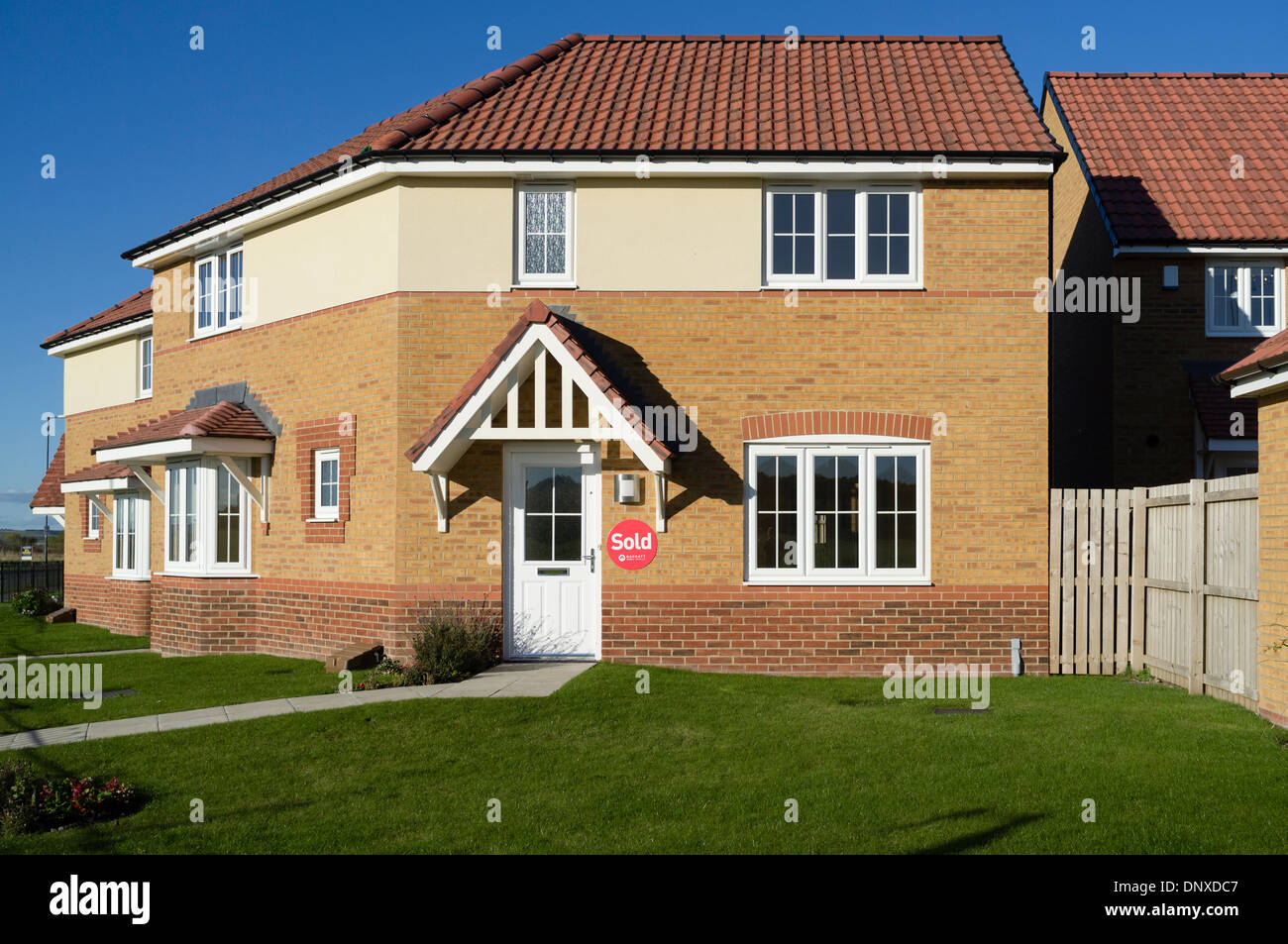 New built Barratt house with Sold sign on wall. - Stock Image