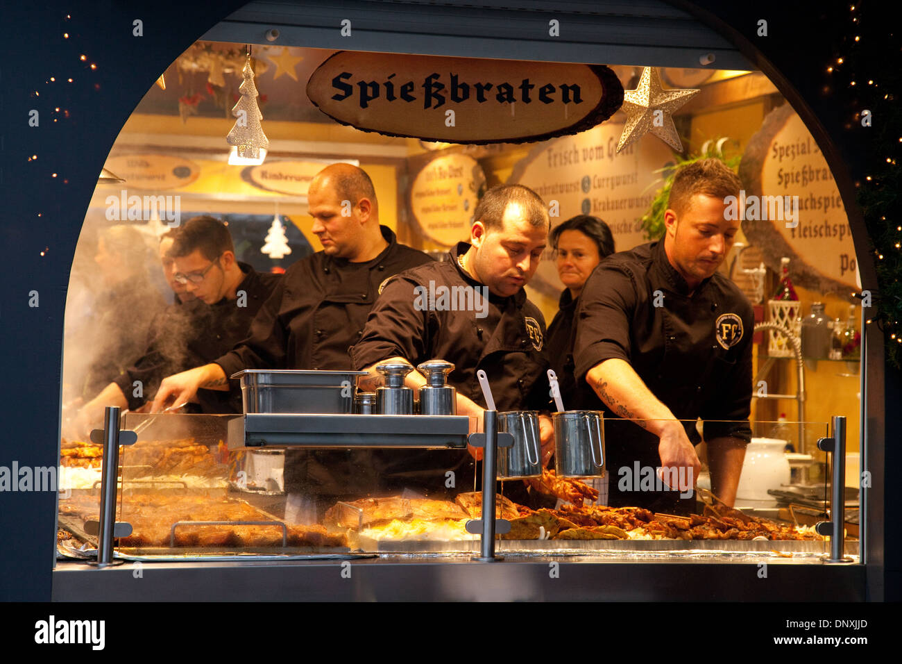 German  Christmas markets Spiessbraten ( Pork steaks) being cooked on a stall in the Cathedral Market, Cologne ( Koln ), Germany - Stock Image