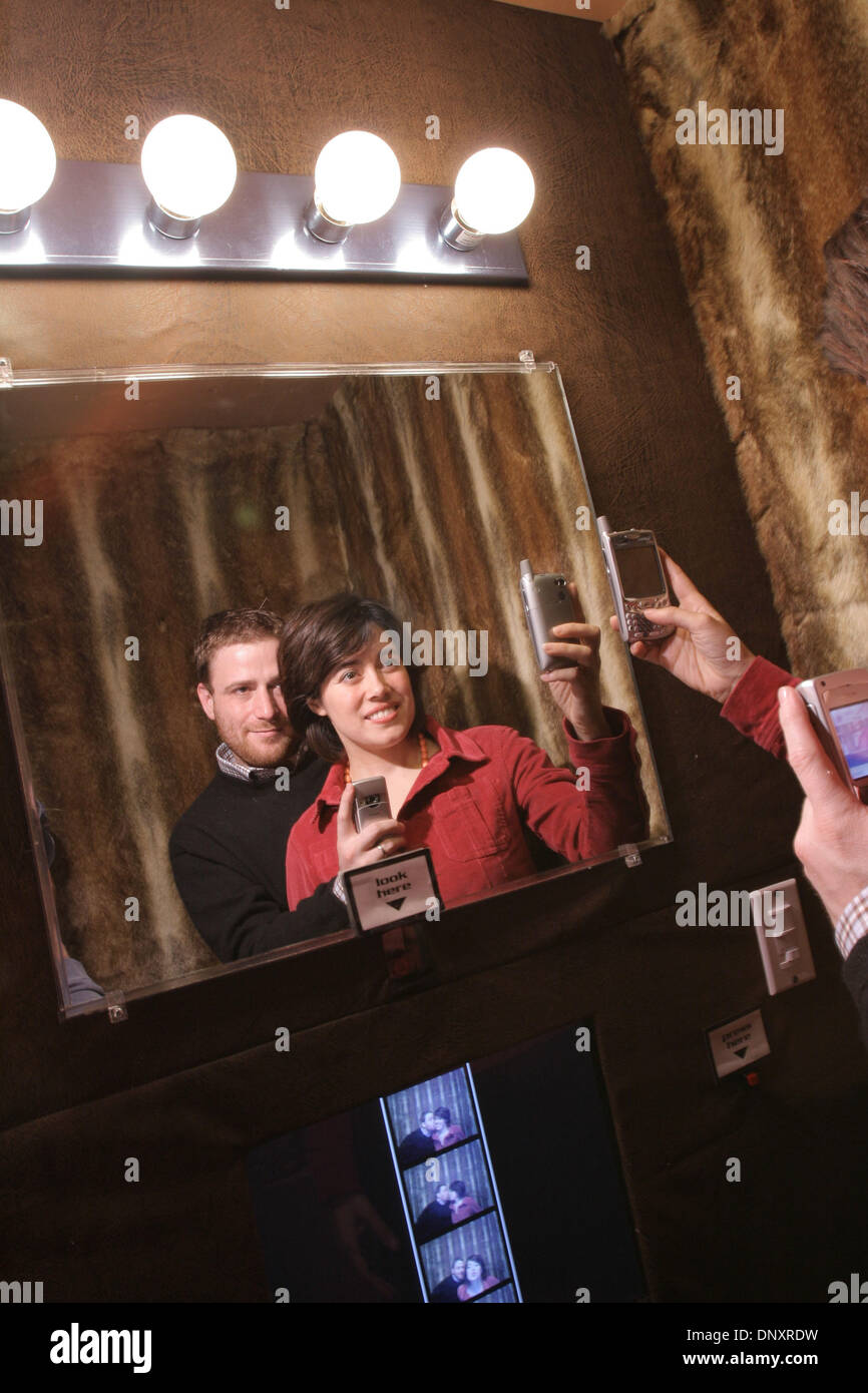 Dec 25, 2006 - San Francisco, CA, USA - Flickr co-founders STEWART BUTTERFIELD and CATERINA FAKE take photos of themselves with their cameraphones as they pose for photos in a Flickr photo booth in a bar called Shine in San Francisco. (Credit Image: © Martin Klimek/ZUMA Press) RESTRICTIONS: Shot for USA Today - Stock Image