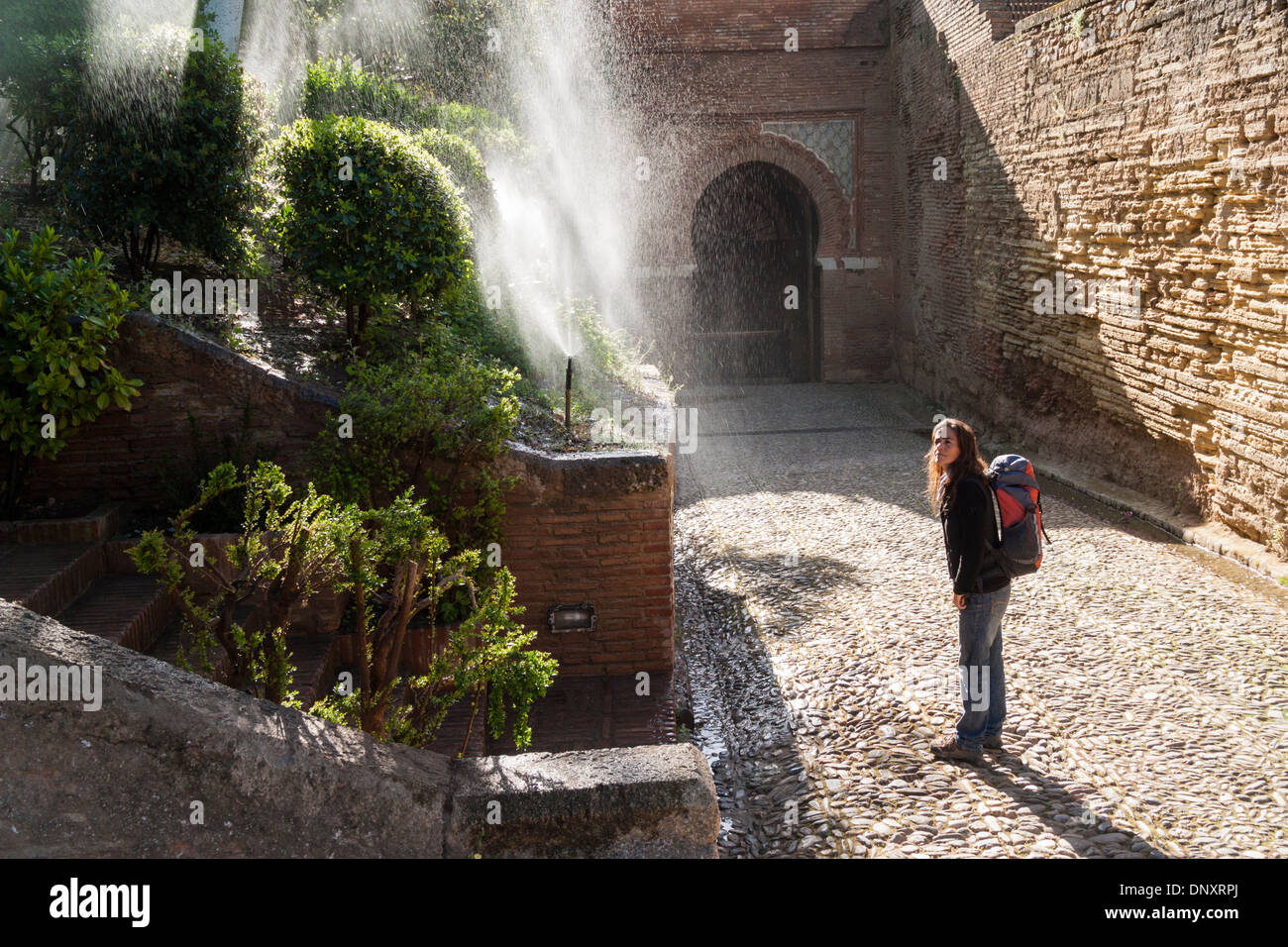 Female tourist cooling down near garden sprinklers on a hot day in La Alhambra, Granada, Andalusia, Spain - Stock Image