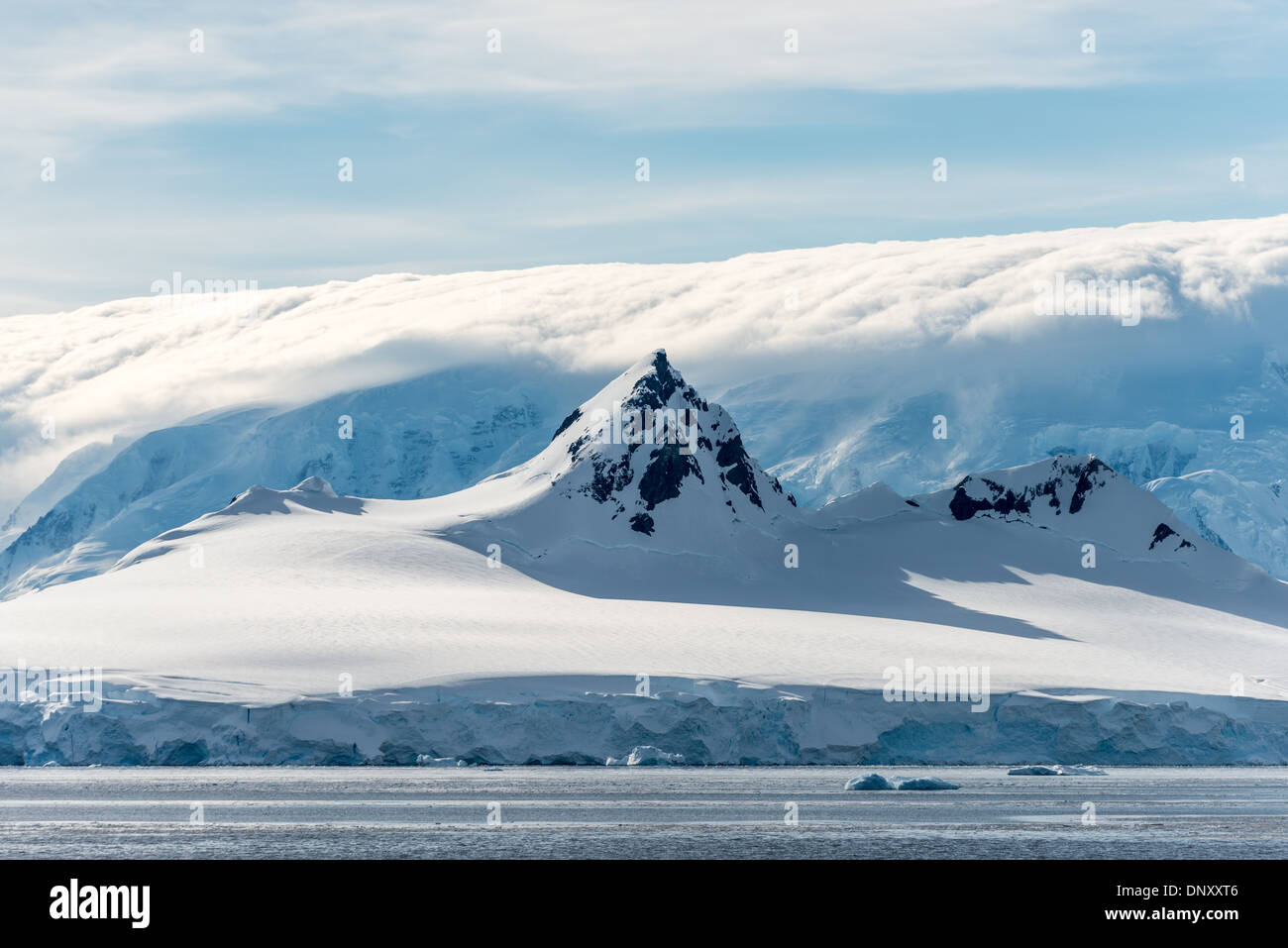 ANTARCTICA - A steep peak rises above the surround mountain, while in the background clouds obscure an even taller Stock Photo