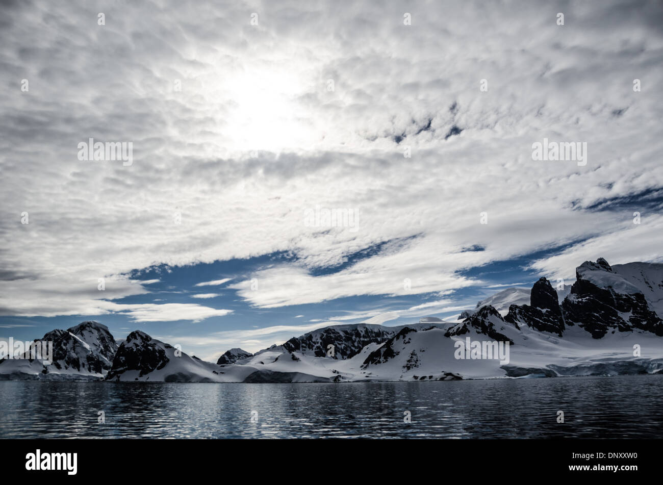 ANTARCTICA - A light layer of high clouds partially obscures the sun above Cuverville Island on the western side Stock Photo