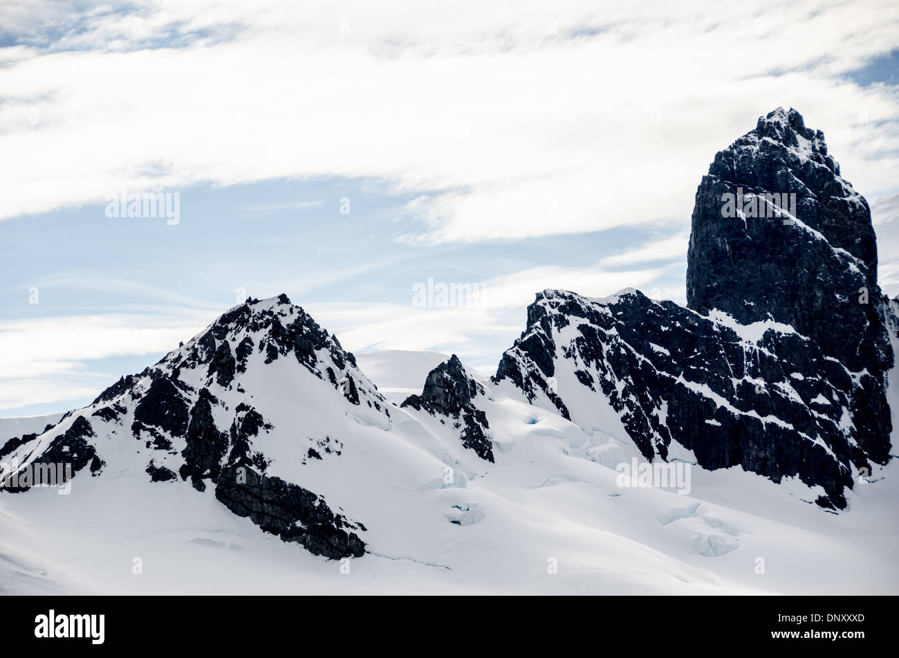 ANTARCTICA - Rugged rocky mountains covered in snow and ice rise up from the Antarctica Peninsula near Cuverville Stock Photo
