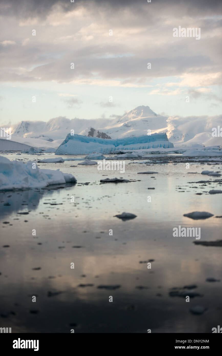 ANTARCTICA - The setting sun casts a beautiful orange glow on clouds and mountains of the dramatic Antarctic landscape of Paradise Harbor, Antarctica. - Stock Image