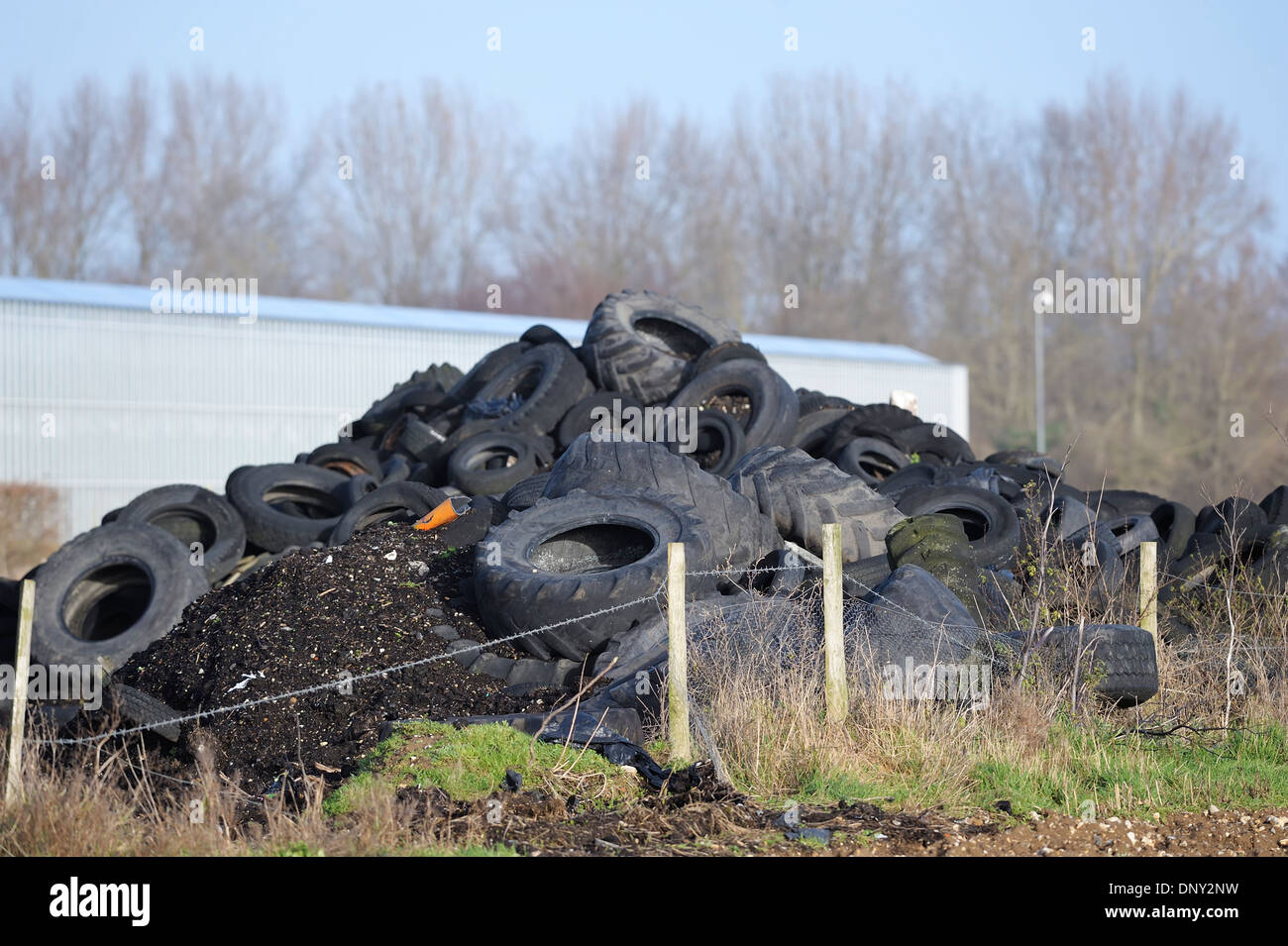 Old used worn out car and lorry tires tyres dumped in a pile with other waste  causing and environmental problem for the future - Stock Image