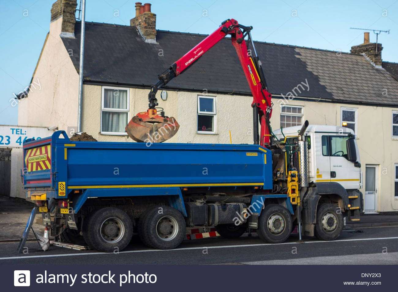 MAN Tipper Grab Truck in use at side of main road - Stock Image