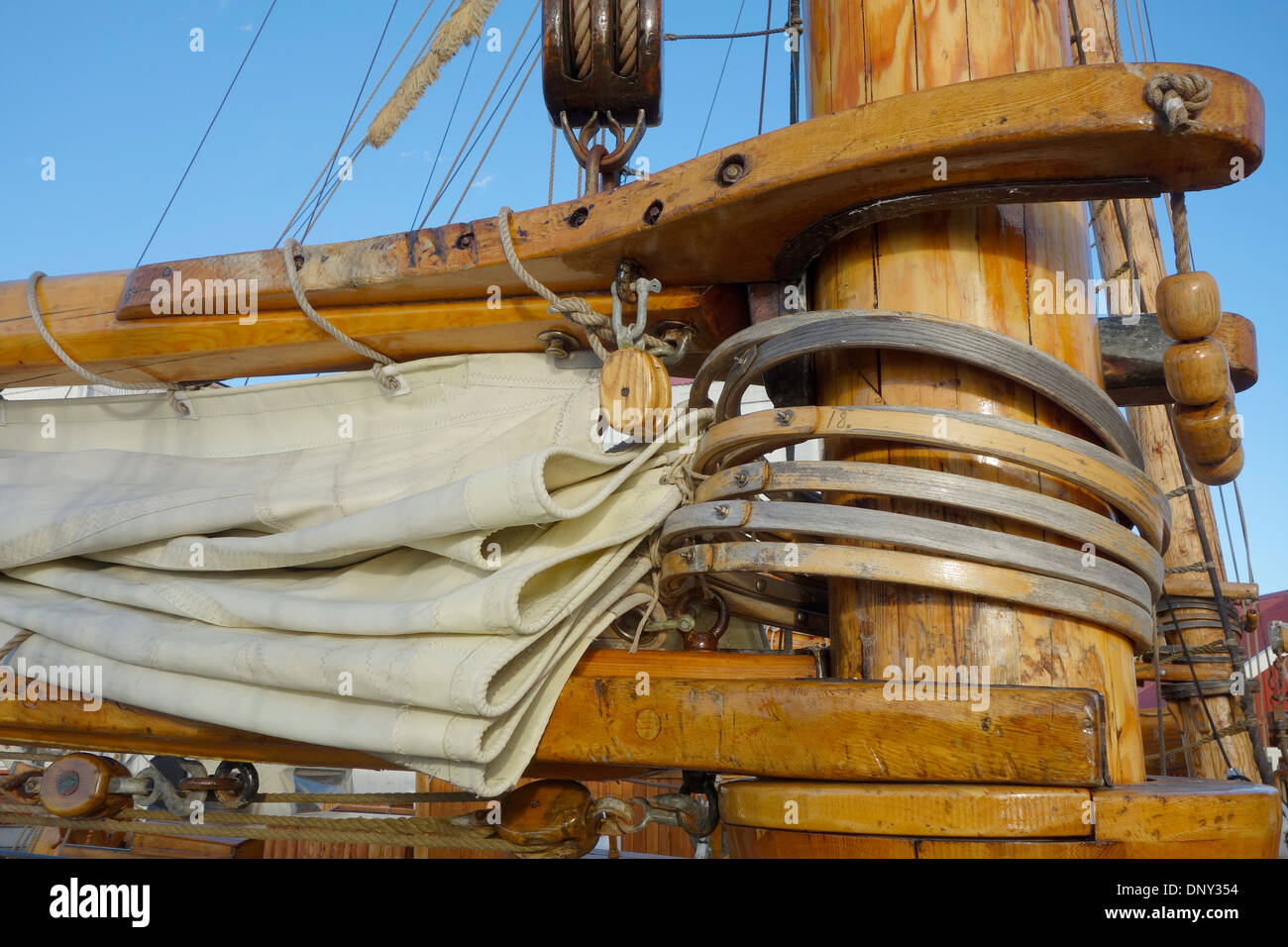 Boom Gaff and Canvas. Detail of boom, gaff and headsail luff with mast hoops around the main mast on a schooner sailship. - Stock Image