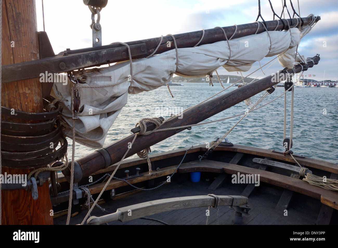 Schooner's stern with details of mizzen mast, boom, gaff and folded spanker sail with luff and mast hoops. - Stock Image