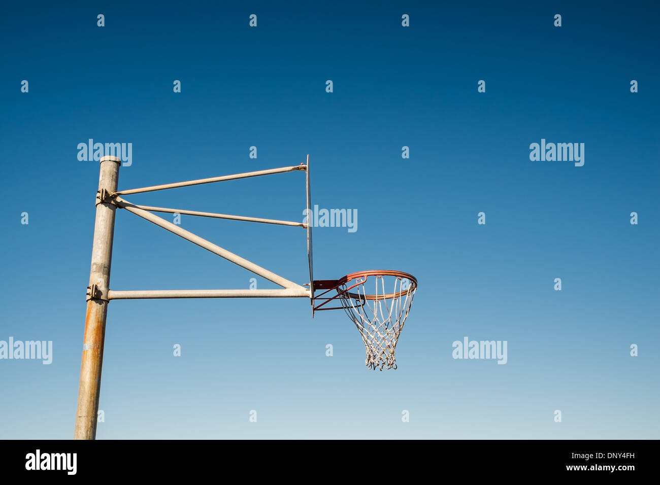 Side view of a basketball hoop against blue sky - Stock Image