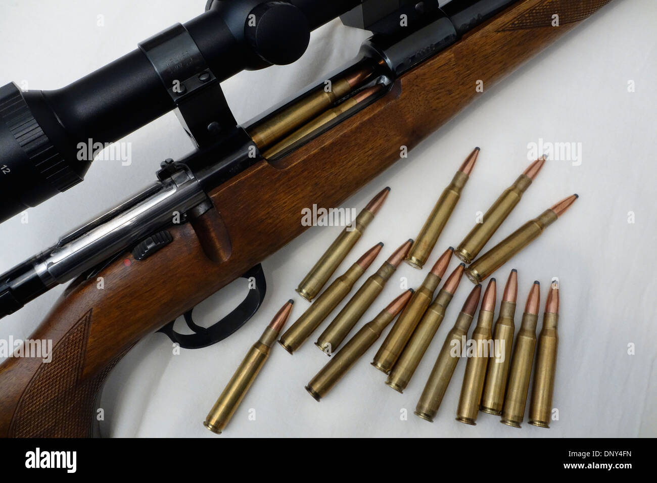 Close up of loaded rifle with telescopic sight. Open bolt and ammo scattered around. - Stock Image