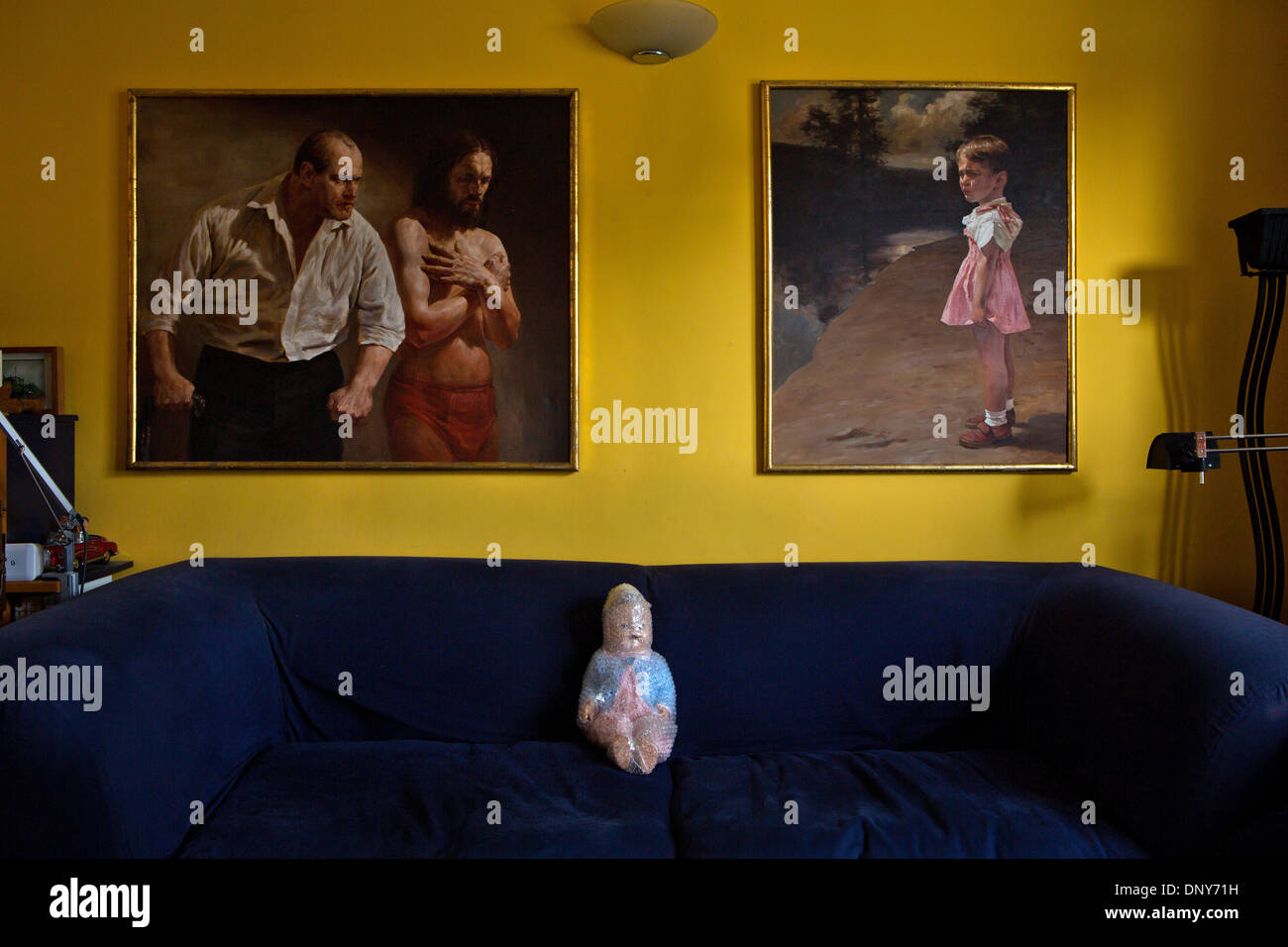 Paintings by the artist Janusz Szpyt on the wall of a London living room. A wrapped doll is sitting on the sofa. - Stock Image