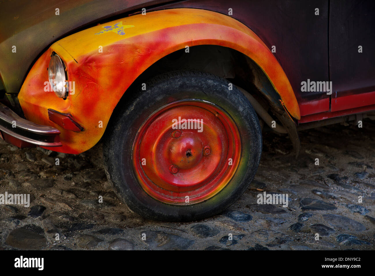 Brightly painted orange & yellow 2CV French car wheel on cobbled street, France - Stock Image
