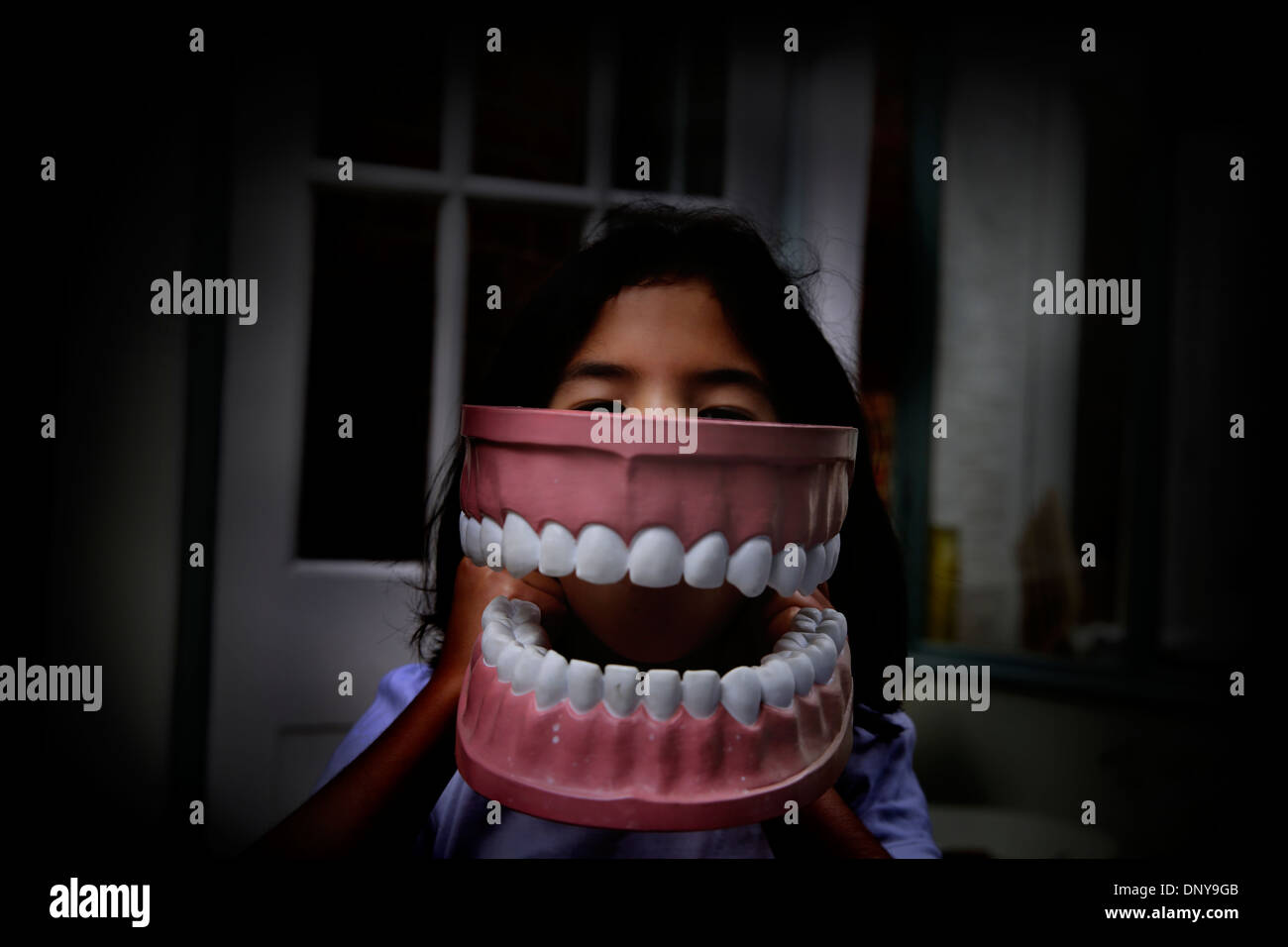 Child playing with giant toy teeth - Stock Image