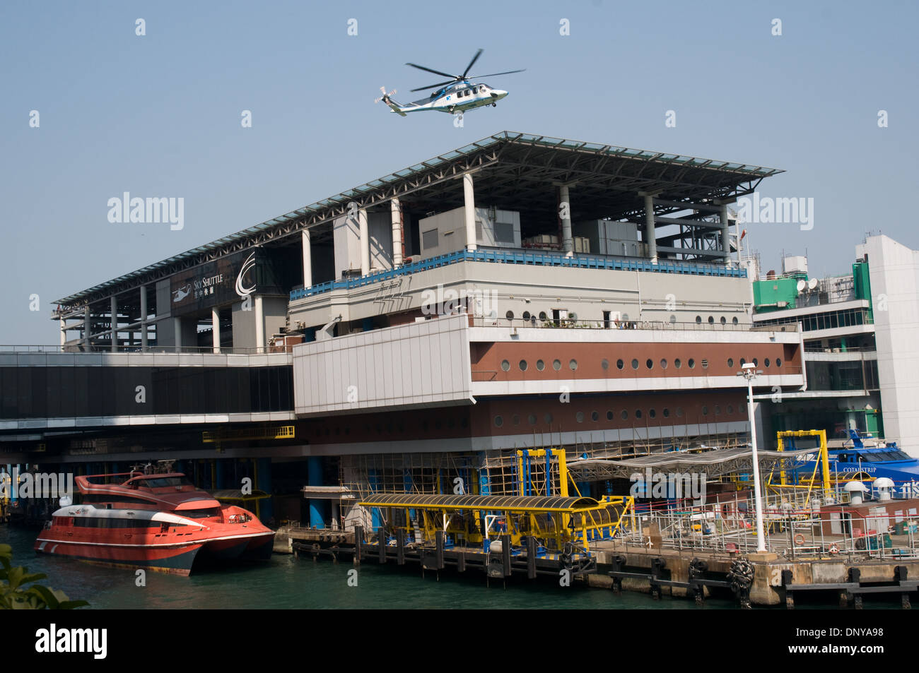 A helicopter lifts off from the Macau Ferry terminal building to fly to Macau. Moored alongside the building are the ferries. - Stock Image