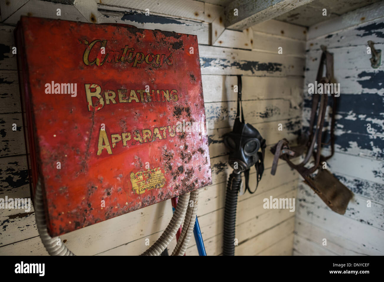 Old safety and firefighting equipment hangs on a wall near an exit at Wordie House. Originally known as Base F and - Stock Image