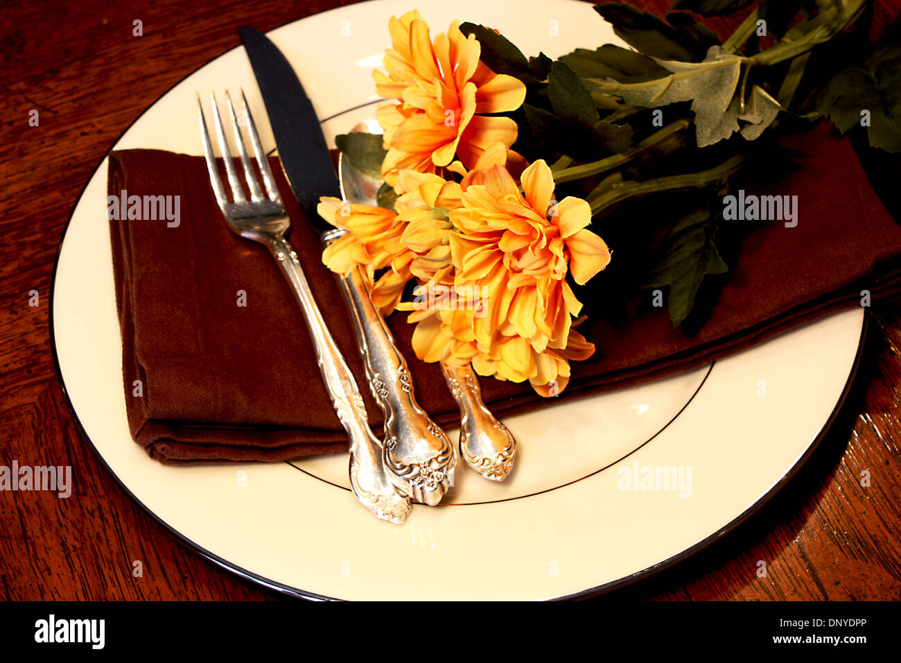 Formal Table Setting with napkin silverware and flowers on a brown table & Formal Table Setting with napkin silverware and flowers on a brown ...